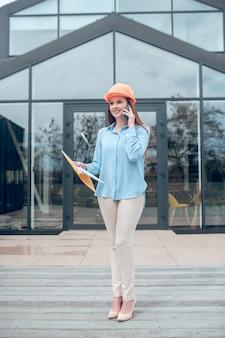 Mujer hablando por teléfono inteligente contra el fondo del edificio