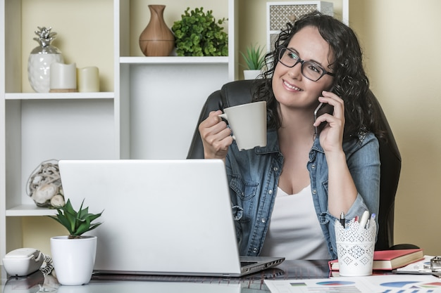 Mujer hablando por teléfono inteligente en la oficina en casa