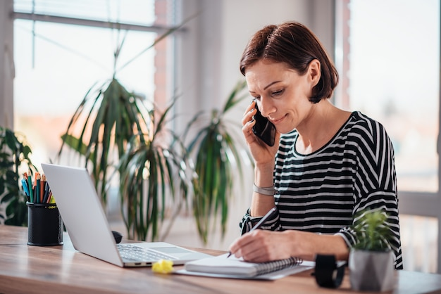 Mujer hablando por teléfono inteligente en la oficina
