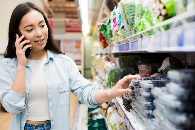 Mujer hablando en teléfono inteligente en la tienda de comestibles