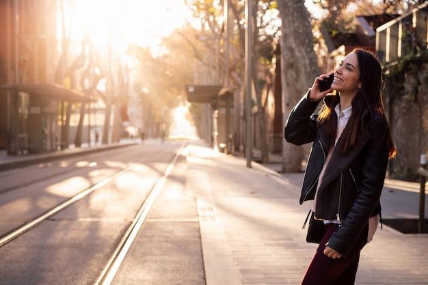 Mujer hablando por teléfono mientras cruza la calle