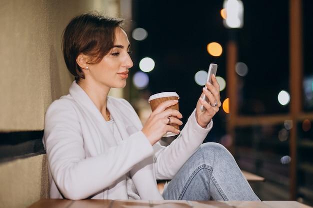 Mujer hablando por teléfono y tomando café afuera en la calle por la noche