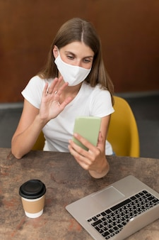 Mujer hablando por videollamada con máscara