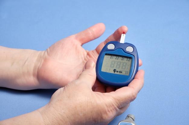 Una mujer hace un análisis de sangre para el azúcar, en un espacio azul. espacio para texto