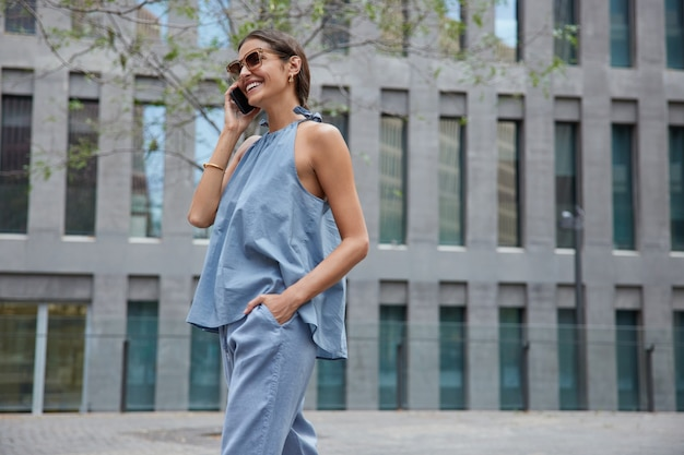 La mujer hace una conversación internacional con un teléfono inteligente, usa un traje de moda, gafas de sol, disfruta de llamadas de teléfono celular, camina al aire libre cerca del edificio de la ciudad moderna