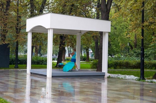 Una mujer hace deporte bajo un dosel en tiempo nublado. lluvia de verano