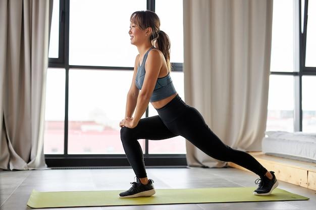 La mujer hace ejercicios para las piernas, fortalece los músculos de las piernas y los glúteos, usa ropa deportiva, en casa