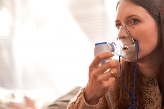La mujer hace la inhalación en casa.