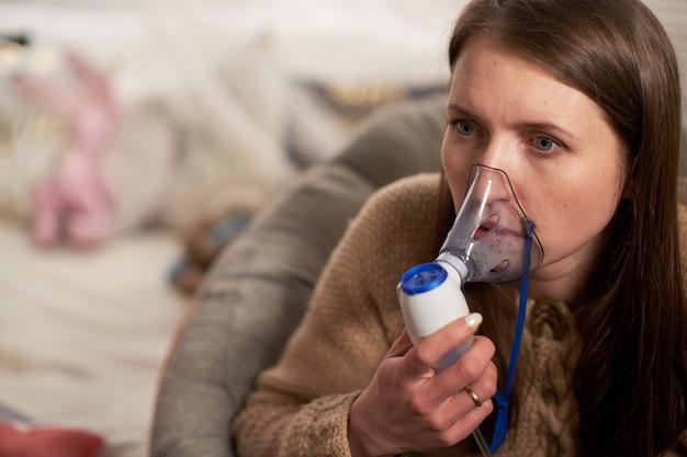 Mujer hace inhalación nebulizador en casa. sosteniendo un nebulizador de máscara inhalando vapores rocíe el medicamento en el paciente enfermo de sus pulmones.