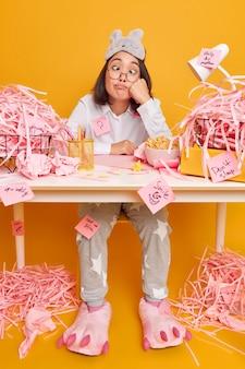 Mujer hace muecas cruza los ojos se sienta en el escritorio vestida con pijama trabaja desde casa plantea en amarillo