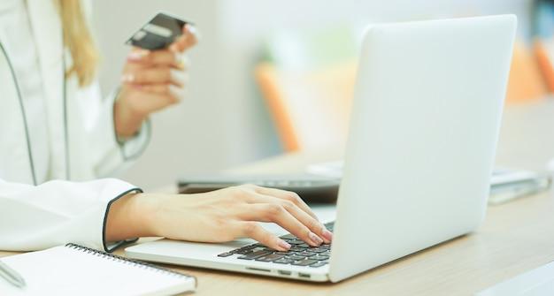 La mujer hace un pago en línea con concepto de la tarjeta de crédito.