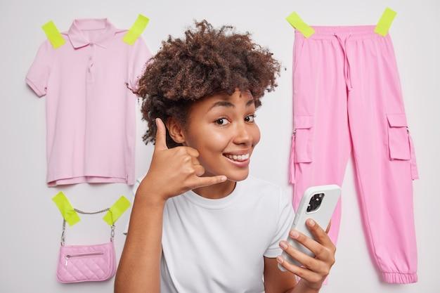 La mujer hace que el gesto me llame tiene un teléfono inteligente moderno pide un número de teléfono posa en blanco con ropa enyesada a la pared blanca tiene un aspecto feliz