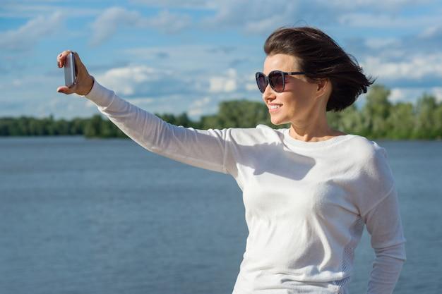 Mujer hace selfie usando teléfono inteligente