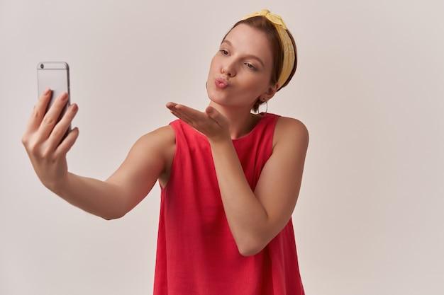 Mujer hacer tiro beso emoción vistiendo verano elegante blusa roja de moda y pañuelo amarillo mirando a un lado en el teléfono inteligente posando en la pared blanca con los brazos gesticula beso mosca