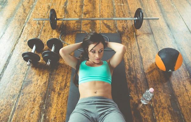 Mujer haciendo abdominales en el piso del gimnasio
