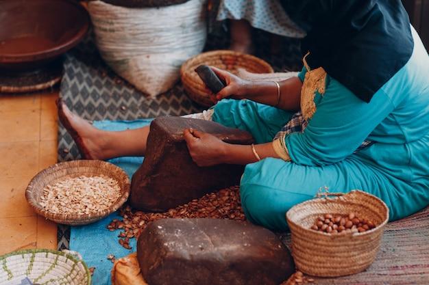 Mujer haciendo aceite de argán a mano