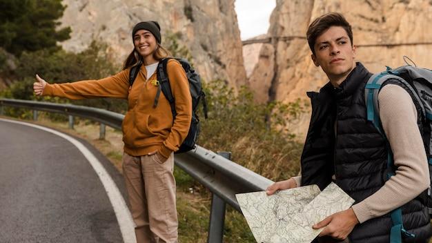 Mujer haciendo autostop para un coche y hombre sujetando el mapa