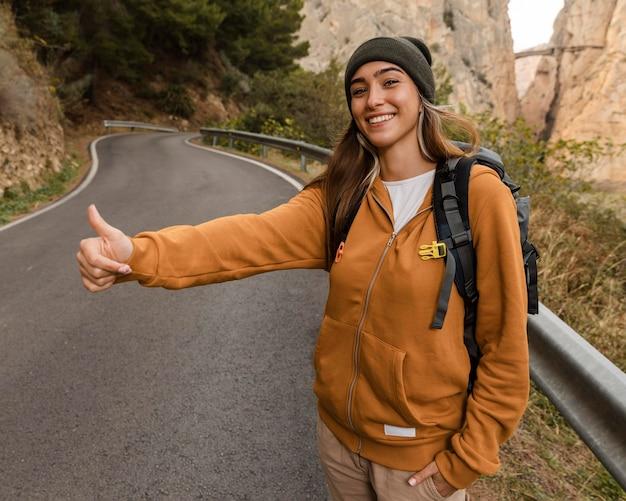 Mujer haciendo autostop para un coche en las montañas