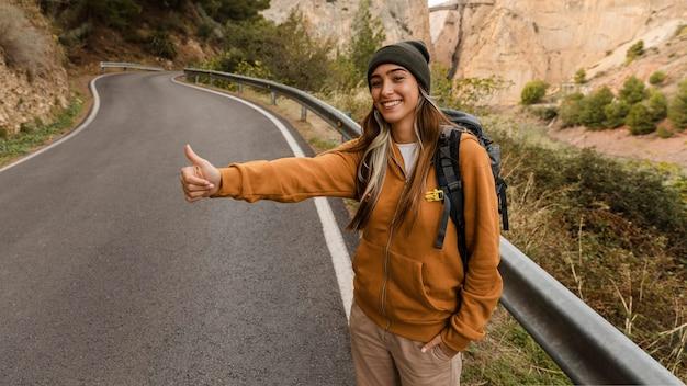 Mujer haciendo autostop para un coche