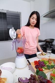 Mujer haciendo batidos vegetales con licuadora en la cocina