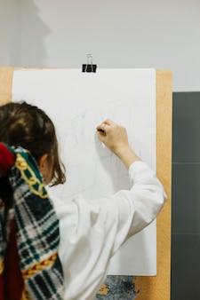 Mujer haciendo boceto en el caballete
