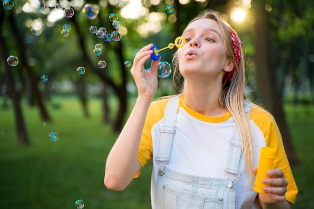 Mujer haciendo burbujas al aire libre