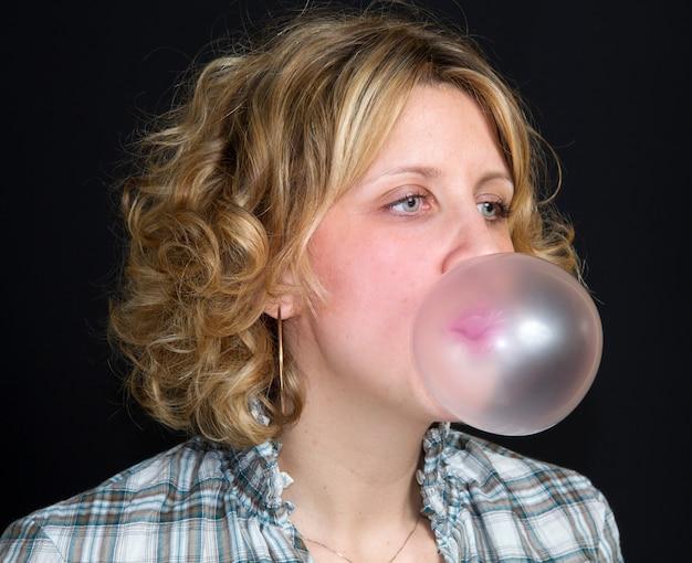 Mujer está haciendo burbujas con chicle