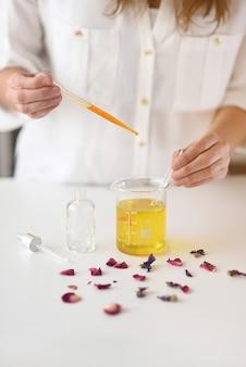 Mujer haciendo cosmética natural en laboratorio con gotero y aceites esenciales