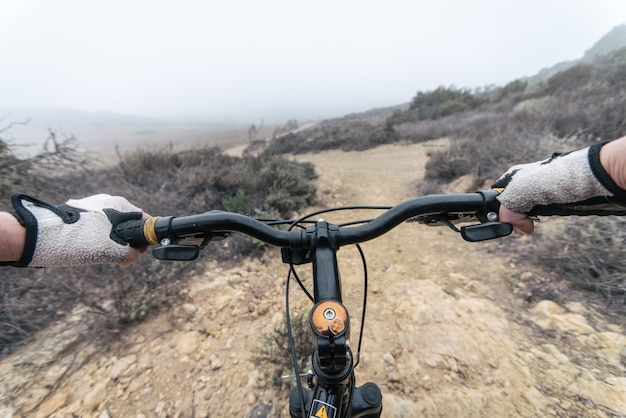 Mujer haciendo cuesta abajo con bicicleta de montaña. concepto sobre personas y deporte.