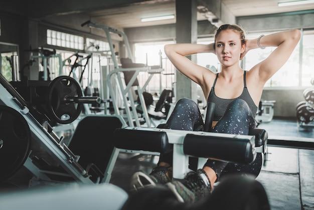 Mujer haciendo decaimiento banco cruje en gimnasio