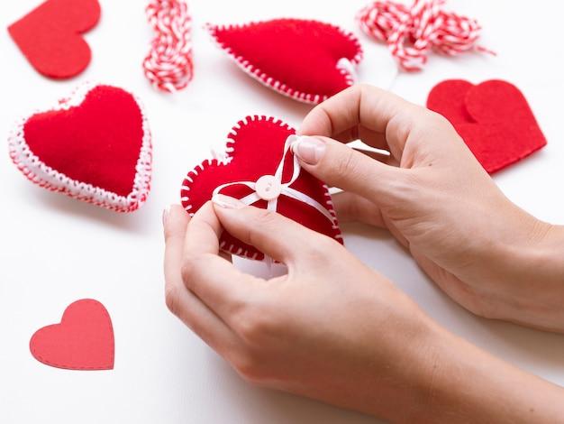 Mujer haciendo decoraciones de corazones rojos
