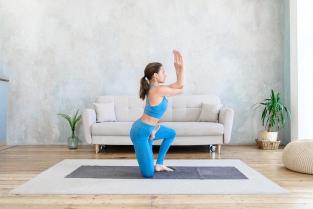 Mujer haciendo deporte en casa haciendo estiramientos de yoga en la habitación