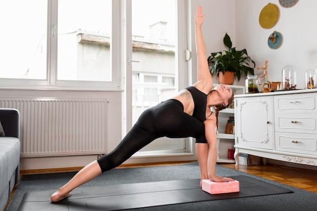 Mujer haciendo deporte de estocada lateral en concepto de hogar