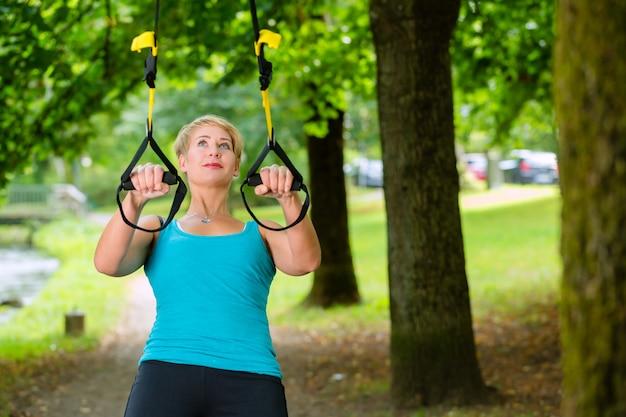 Mujer haciendo deporte de suspensión de la honda entrenador