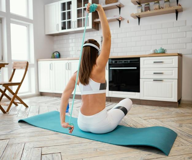 Mujer haciendo ejercicio con banda elástica mientras escucha música