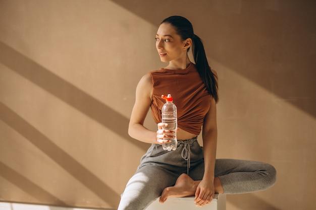 Mujer haciendo ejercicio y bebiendo agua.