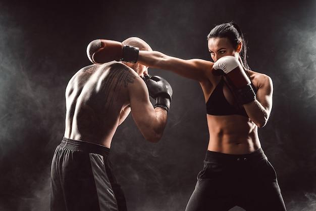 Mujer haciendo ejercicio con entrenador en la lección de boxeo y defensa personal, estudio, humo en el espacio