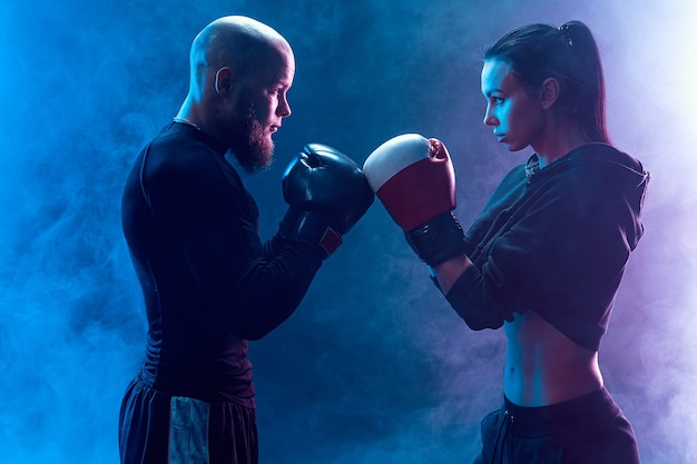 Mujer haciendo ejercicio con entrenador en la lección de boxeo y defensa personal
