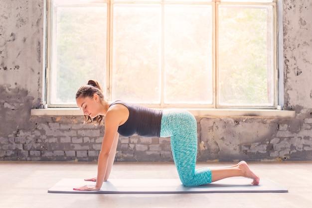Mujer haciendo ejercicio en la estera del ejercicio