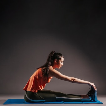 Mujer haciendo ejercicio en la estera de estiramiento