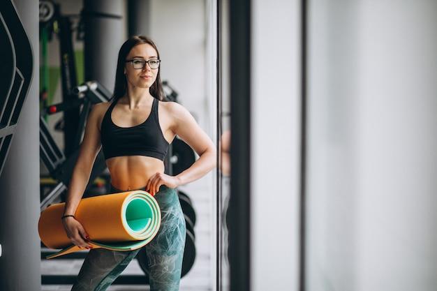 Mujer haciendo ejercicio en el gimnasio con colchoneta de yoga