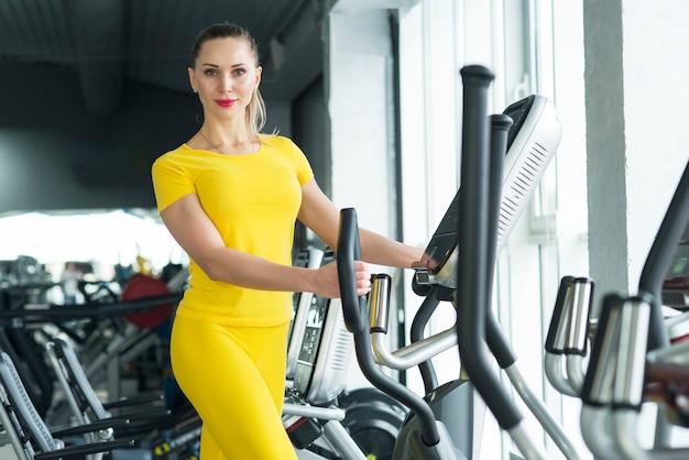 Mujer haciendo ejercicio en el gimnasio en un entrenador elíptico entrenamiento cardiovascular