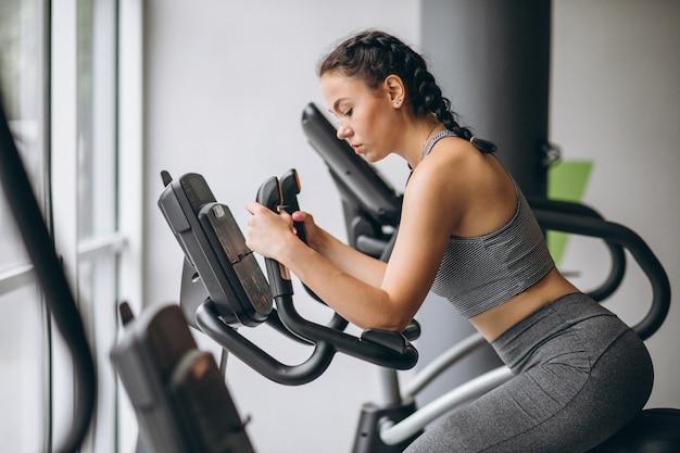 Mujer haciendo ejercicio en el gimnasio sola