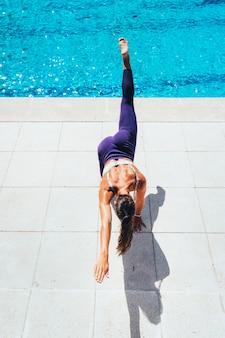 Mujer haciendo ejercicio gimnástico al lado de la piscina