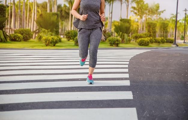 Mujer haciendo ejercicio. mujer corredor corriendo por la mañana en el parque público.
