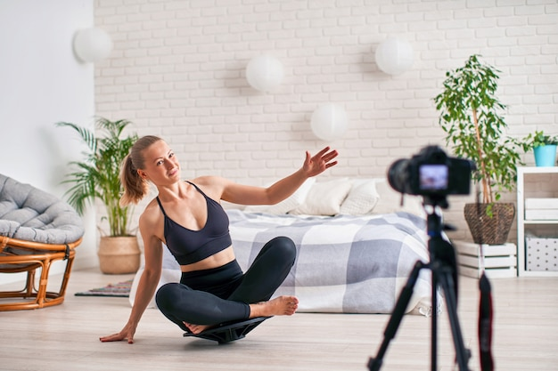 Mujer haciendo ejercicio en un simulador especial equilibrador. ropa deportiva atlética rubia, el ejercicio en casa fortalece los músculos.