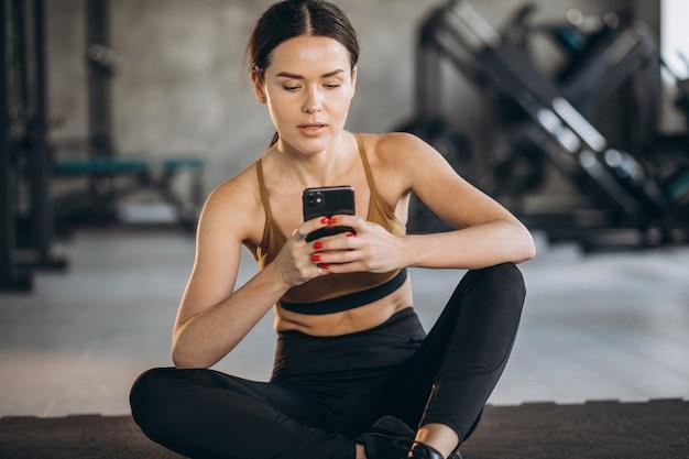 Mujer haciendo ejercicio a través del programa en línea en el gimnasio
