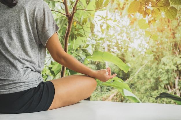 Mujer haciendo ejercicio de yoga pose vital y meditación en fondo natural.