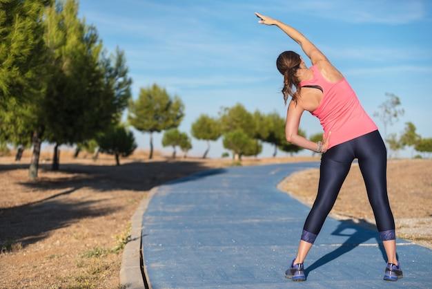 Mujer haciendo ejercicios de estiramiento para espalda, fondo deportivo.