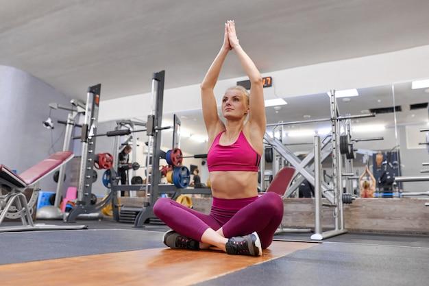 Mujer haciendo ejercicios de estiramiento en el gimnasio, mujer practicando yoga